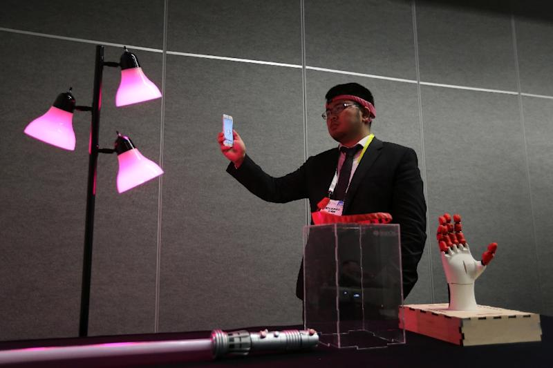 BrainCo CEO Bicheng Han wears the BrainCo Focus 1 to use bio feedback to change the color of a lamp by concentrating or relaxing during a press conference at the CES 2016 Consumer Electronics Show on January 7, 2016 in Las Vegas, Nevada (AFP Photo/David McNew)