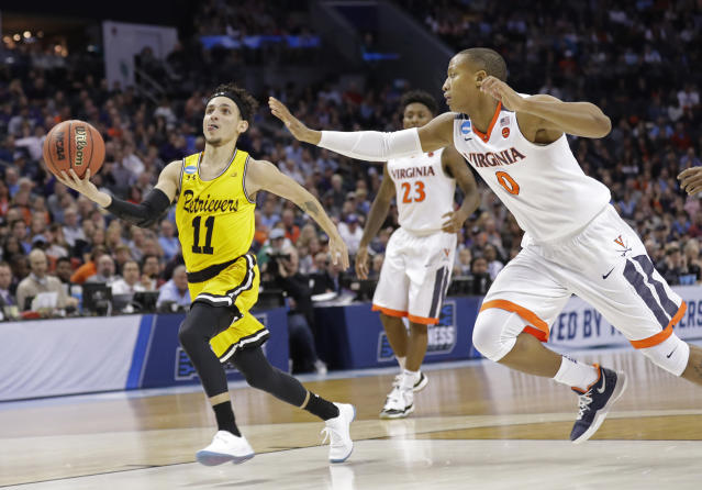 UMBC's K.J. Maura (11) drives past Virginia's Devon Hall (0) during the second half of the Retrievers' historic upset of the Cavaliers in the 2018 NCAA tournament. (AP)
