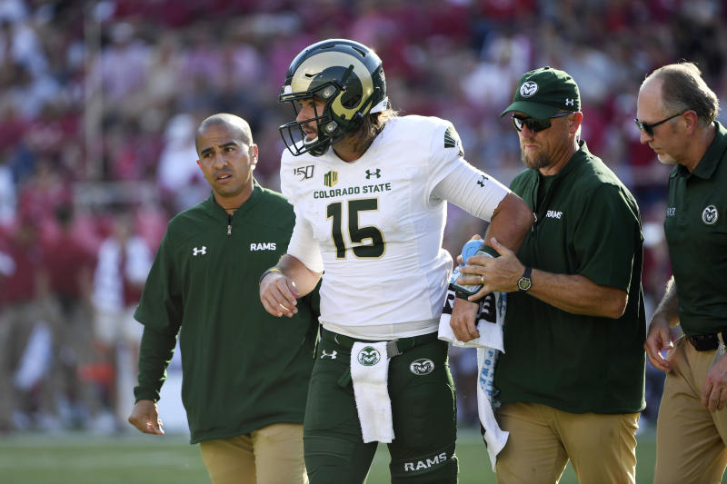 Colorado State quarterback Collin Hill is helped off the field after being injured against Arkansas during an NCAA football game on Saturday, Sept. 14, 2019 in Fayetteville, Ark. (AP Photo/Michael Woods)