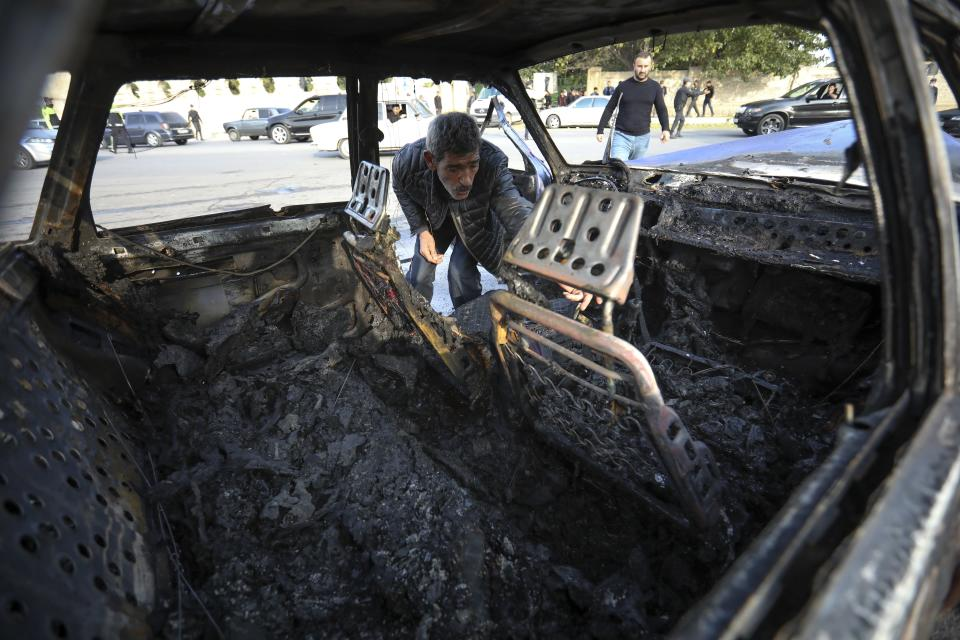 A man looks in a burnt out car after multiple rocket system shelling by Armenian forces in Barda, Azerbaijan, Wednesday, Oct. 28, 2020. The Azerbaijani Defense Ministry rejected all the accusations and in turn accused Armenian forces of using the Smerch multiple rocket system to fire at the Azerbaijani towns of Terter and Barda. The strike on Barda killed more than 20 people and wounded 60, Azerbaijani officials said. (AP Photo/Aziz Karimov)