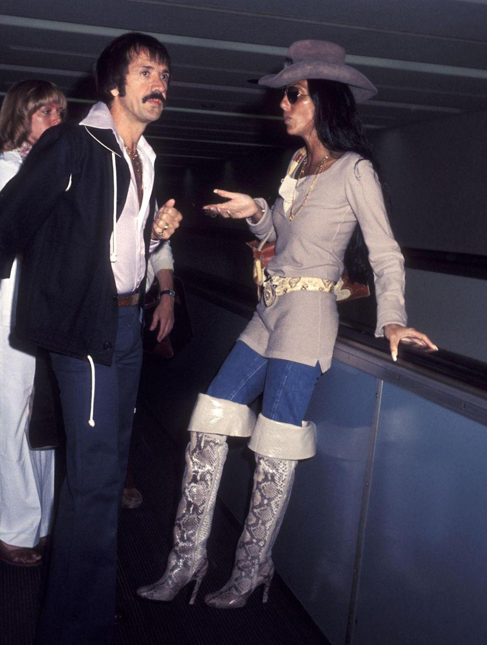 <p>Arriving to the airport in a cowboy hat and snake print over-the-knee boots with Sonny. </p>