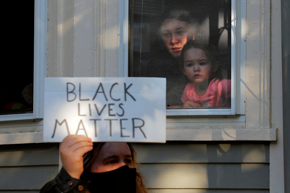 A woman and a girl watch from window as demonstrators pass by protesting against racial inequality in the aftermath of the death in Minneapolis police custody of George Floyd in Salem, Massachusetts, U.S., June 12, 2020.   (Brian Snyder/Reuters)