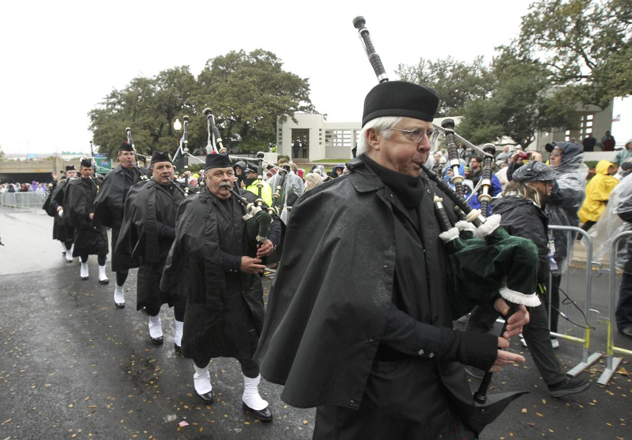 The Dallas Metro Police Pipes and Drums corps march up Elm Street where President John F. Kennedy was shot, at the conclusion of ceremonies marking the 50th anniversary of the assassination of President John F. Kennedy in Dallas, Texas November 22, 2013. REUTERS/Jim Bourg (UNITED STATES - Tags: POLITICS ANNIVERSARY MILITARY)