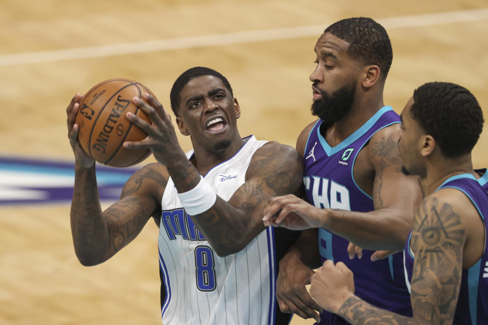 Orlando Magic guard Dwayne Bacon, left, drives to the basket against Charlotte Hornets guard Brad Wanamaker and forward P.J. Washington, right, during the second half of an NBA basketball game in Charlotte, N.C., Friday, May 7, 2021. (AP Photo/Nell Redmond)