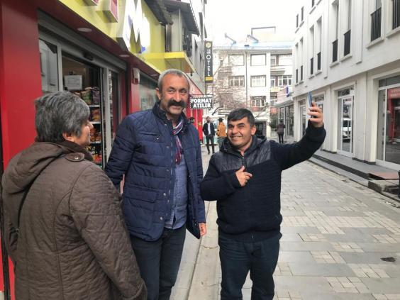 Macoglu (centre) meets constituents on the streets of Tunceli (Borzou Daragahi/The Independent)