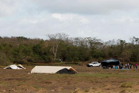 Police and forensic team use tents to mark some of the unmarked graves where skulls were found in a plot of land on the outskirts of Veracruz, Mexico March 16, 2017. REUTERS/Carlos Jasso