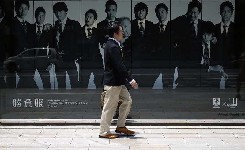 A man walks past a display window of a luxury brand at Tokyo's Ginza shopping district