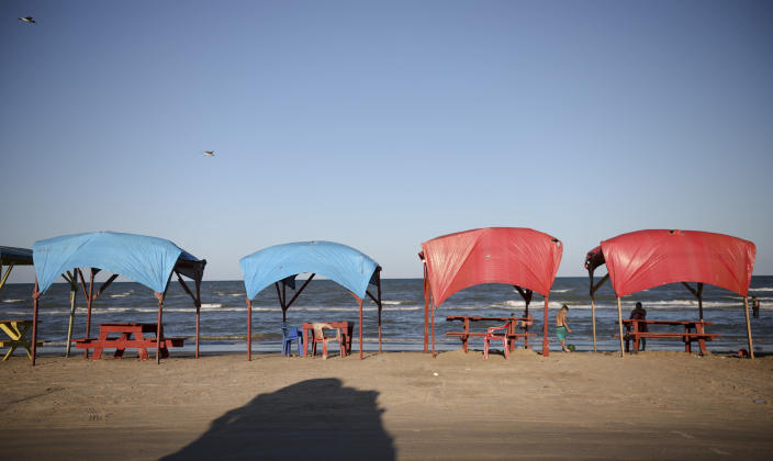 In this Aug. 2, 2019 photo, picnic tables shaded by tarps line the shoreline in Playa Bagdad close to the mouth of the Rio Grande near the border city of Matamoros, Mexico. The only highway that reaches here ends abruptly in a handful of huts populated by beachgoers looking for alcohol and fishermen who might catch sharks one day, and unload cocaine the next. (AP Photo/Emilio Espejel)