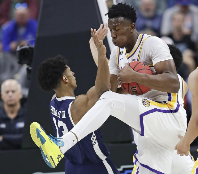 LSU's Kavell Bigby-Williams, right, grabs a rebound away from Yale 's Trey Phills during the first half of a first round men's college basketball game in the NCAA Tournament, in Jacksonville, Fla. Thursday, March 21, 2019. (AP Photo/John Raoux)