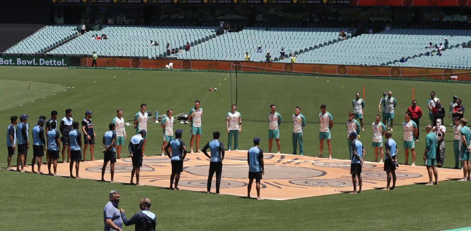 Players stand for a ceremony on the field ahead of the one day international cricket match between India and Australia at the Sydney Cricket Ground in Sydney, Australia, Friday, Nov. 27, 2020. (AP Photo/Rick Rycroft)