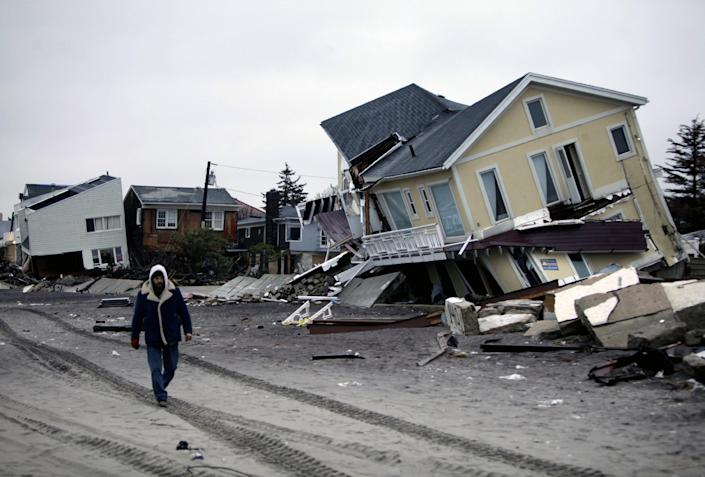 FILE - In this Tuesday, Nov. 27, 2012 file photo, a man walks past destroyed homes on the Rockaway Peninsula in Queens, New York. Delegates from nearly 200 countries are meeting in the Qatari capital of Doha to discuss ways slowing climate change, including by cutting emissions of greenhouse gases that scientists say are warming the planet, melting ice caps, raising sea levels, and changing rainfall patterns with impacts on floods and droughts (AP Photo/Seth Wenig, File)