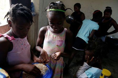 Children eat in a partially destroyed orphanage after Hurricane Matthew passes Jeremie, Haiti, October 11, 2016. REUTERS/Carlos Garcia Rawlins