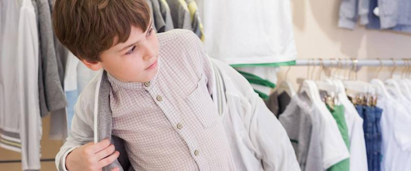 The boy tries on clothes in the childrens clothing store