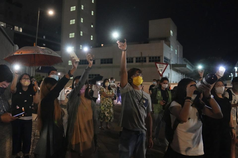 Supporters wave flashlights outside the Apple Daily headquarters in Hong Kong, Wednesday, June 23, 2021. Hong Kong's pro-democracy Apple Daily newspaper will stop publishing Thursday, following last week's arrest of five editors and executives and the freezing of $2.3 million in assets under the city's one-year-old national security law. (AP Photo/Kin Cheung)