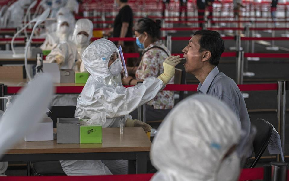 Refrigerated meat, seafood and other frozen productshave all been tossed at Xinfadi market - Getty Images AsiaPac/A Chinese epidemic control worker wears a protective suit as she performs a nucleic acid swab test for COVID-19 on a man at a government testing site in Xicheng District