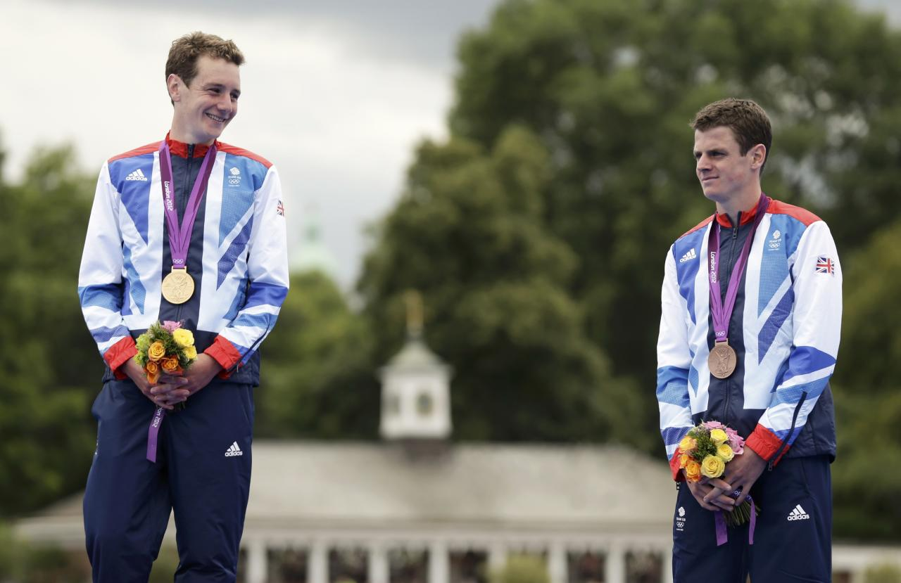 Britain's Alistair Brownlee (L) celebrates his gold medal with his brother Jonathan Brownlee who placed third after the men's triathlon final during the London 2012 Olympic Games at Hyde Park August 7, 2012.                 REUTERS/Tim Wimborne (BRITAIN  - Tags: OLYMPICS SPORT TRIATHLON TPX IMAGES OF THE DAY)