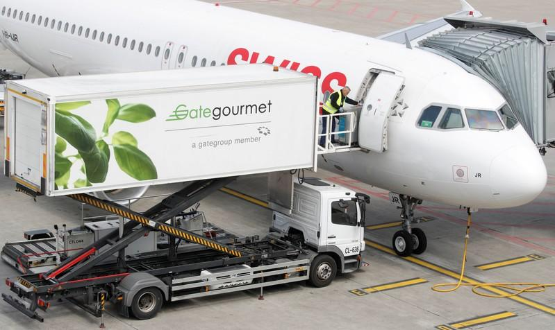 FILE PHOTO: Gate Gourmet staff loads a trolley aboard an Airbus A320-214 of Swiss airlines at Zurich airport