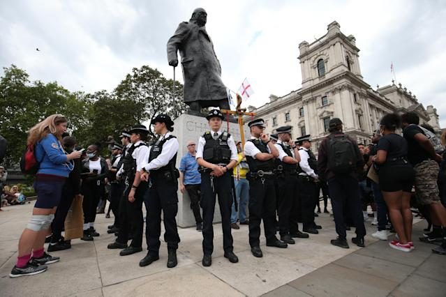 Police stand guard around the Sir Winston Churchill statue in Parliament Square, Westminster, on Tuesday. (PA)