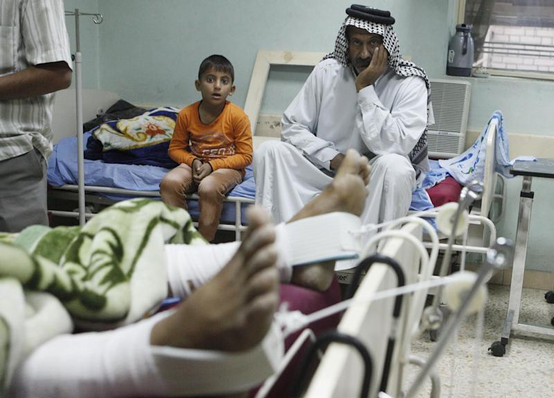 Khalid Abdullah lies in a hospital bed a day after being injured in a bomb blast as his son Mohammed Khalid, 6, left, and his father Abdullah Mahdi, 57, sit next to him at a hospital in the Shiite enclave of Sadr City, in Baghdad, Iraq, Sunday, Oct. 28, 2012. Iraqi insurgents unleashed a string of bombings and other attacks that killed and wounded scores of people, primarily targeting the country's Shiite community on Saturday, Oct. 27, 2012, in a challenge to government efforts to promote a sense of stability by preventing attacks during a major Muslim holiday. (AP Photo/Karim Kadim)