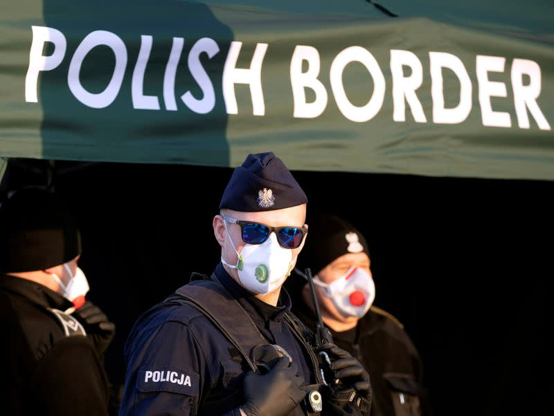 FILE PHOTO: Police officer, wearing protective mask, stands at border between Germany and Poland