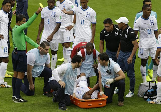 Referee Sandro Ricci from Brazil, left, books Honduras' Wilson Palacios, bottom on a stretcher, during the group E World Cup soccer match between France and Honduras at the Estadio Beira-Rio in Porto Alegre, Brazil, Sunday, June 15, 2014. (AP Photo/Andrew Medichini)