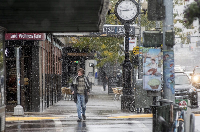 A pedestrian crosses Front Street under snowfall in Missoula, Mont., Sunday, Sept. 29, 2019. Montana Gov. Steve Bullock declared an emergency Sunday, allowing the state to mobilize resources to help affected areas. (Ben Allan Smith/The Missoulian via AP)