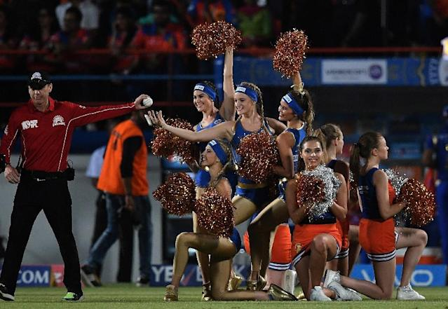 Novel entertainment: An umpire takes the match ball from cheerleaders during an IPL match (AFP Photo/PRAKASH SINGH)