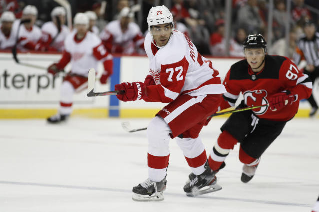 Detroit Red Wings left wing Andreas Athanasiou (72) passes with New Jersey Devils left wing Nikita Gusev (97) pursuing him during the first period of an NHL hockey game, Thursday, Feb. 13, 2020, in Newark, N.J. (AP Photo/Kathy Willens)