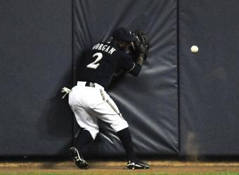 Brewers center fielder Nyjer Morgan slams into the outfield wall chasing a ball hit by Albert Pujols in the third inning of Monday's Game 2. The play resulted in an RBI double for Pujols
