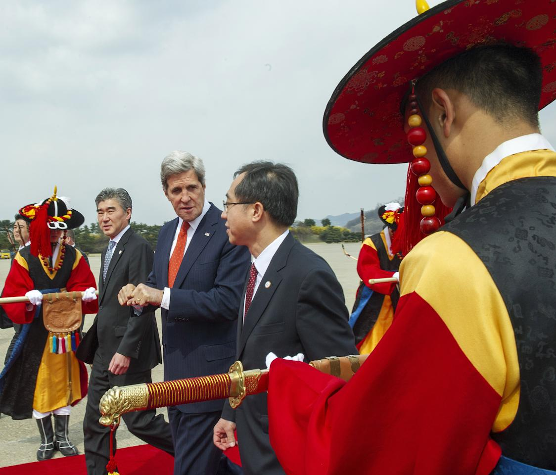 U.S. Secretary of State John Kerry, third left, is escorted by U.S. Ambasador to South Korea Sung Y. Kim, second left, and Deputy director general of South Korea's Foriegn Ministry, Moon Seoung-hyun, center, upon arrival at Seoul air base in Seoul, Friday, April 12, 2013. Kerry arrived in South Korea on Friday on an unusual diplomatic journey, traveling directly into a region bracing for a possible North Korean missile test and risking that his presence alone could spur Pyongyang into another headline-seeking provocation. (AP Photo/Paul J. Richards, Pool)