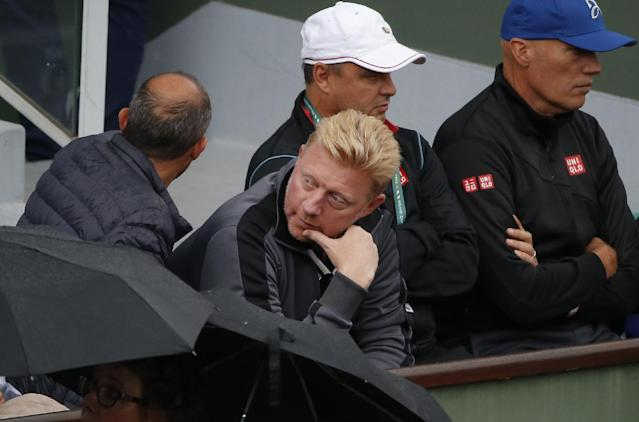 Former German tennis ace Boris Becker, center, watches Serbia's Novak Djokovic playing Portugal's Joao Sousa during their first round match of the French Open tennis tournament at the Roland Garros stadium, in Paris, France, Monday, May 26, 2014. (AP Photo/Michel Euler)