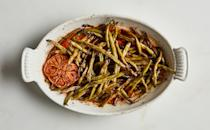 """Toss green beans with tons of olive oil and aromatics and surrender the whole thing to your oven for an hour or two until it becomes impossibly soft and caramelized. <a href=""""https://www.bonappetit.com/recipe/slow-cooked-green-beans-with-harissa-and-cumin?mbid=synd_yahoo_rss"""" rel=""""nofollow noopener"""" target=""""_blank"""" data-ylk=""""slk:See recipe."""" class=""""link rapid-noclick-resp"""">See recipe.</a>"""