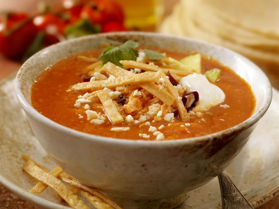 "<p>The flavors in this soup taste like they took hours and hours to come together, but it's pretty easy to make. For this dish, chicken breasts, a can of diced tomatoes, cilantro, warm spices like cumin and chili powder and other ingredients are simmered together in a base of chicken stock and bay leaves. The classic Tex-Mex chicken tortilla soup is topped with crunchy tortilla strips, Monterey Jack cheese, sour cream and cubed avocado. Now that's a <a href=""https://www.thedailymeal.com/cook/what-to-do-with-leftover-chicken?referrer=yahoo&category=beauty_food&include_utm=1&utm_medium=referral&utm_source=yahoo&utm_campaign=feed"" rel=""nofollow noopener"" target=""_blank"" data-ylk=""slk:brilliant way to use your leftover chicken."" class=""link rapid-noclick-resp"">brilliant way to use your leftover chicken.</a></p> <p> <a href=""https://www.thedailymeal.com/recipes/chicken-tortilla-soup?referrer=yahoo&category=beauty_food&include_utm=1&utm_medium=referral&utm_source=yahoo&utm_campaign=feed"" rel=""nofollow noopener"" target=""_blank"" data-ylk=""slk:For the Chicken Tortilla Soup recipe, click here."" class=""link rapid-noclick-resp"">For the Chicken Tortilla Soup recipe, click here.</a></p>"