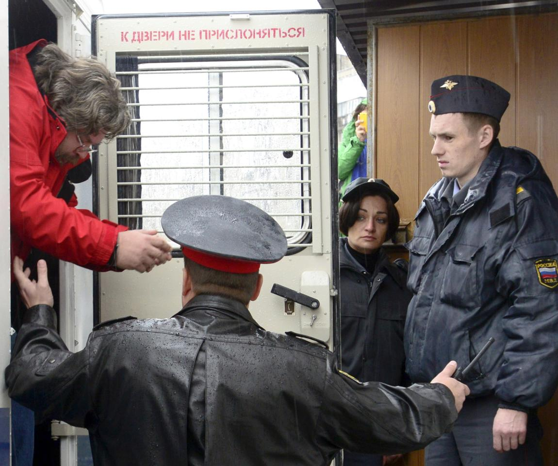 Greenpeace International spokesperson Roman Dolgov (L) is escorted to a district court building in Murmansk, September 26, 2013. Russian President Vladimir Putin said on Wednesday that the activists had violated international law but signalled they should not face charges of piracy. Russian authorities seized the activists' ship, the Arctic Sunrise, and towed it to shore after two of the activists tried to scale the rig to protest against Russian plans to drill for oil in the Arctic, which they say poses a threat to the fragile eco-system. REUTERS/Stringer (RUSSIA - Tags: CRIME LAW ENERGY BUSINESS TPX IMAGES OF THE DAY)