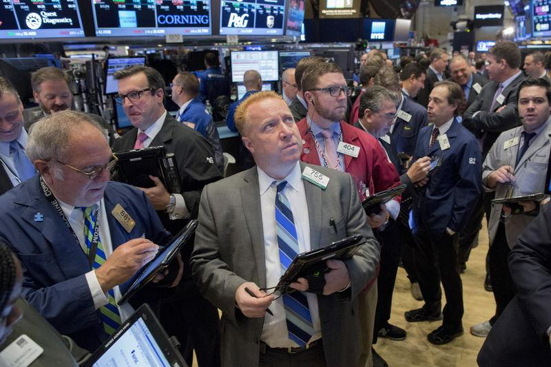 Traders gather at the post that trades Intercontinental Exchange Inc. on the floor of the New York Stock Exchange