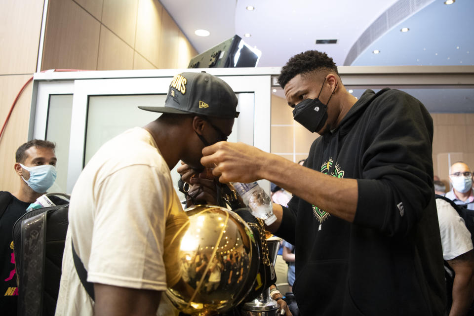 NBA Champion Giannis Antetokounmpo, right, of the Milwaukee Bucks, who was named NBA Finals Most Valuable Player, adjusts his brother's Thanasis face mask at the Eleftherios Venizelos International Airport, in Athens, Greece, Sunday, Aug. 1, 2021. The NBA champion and finals MVP plans to stay in Greece for a few days, before returning to the U.S., where his girlfriend expects their second child later this month. (AP Photo/Michael Varaklas)
