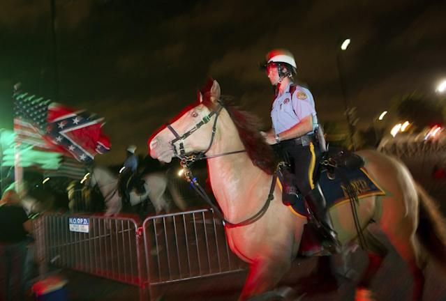 <p>New Orleans Police mounted patrol officers keep watch over a crowd that gathered to watch the removal of a statue of Confederate Gen. P.G.T. Beauregard Wed., May 17, 2017, from the entrance to City Park in New Orleans. (Photo: Scott Threlkeld/AP) </p>