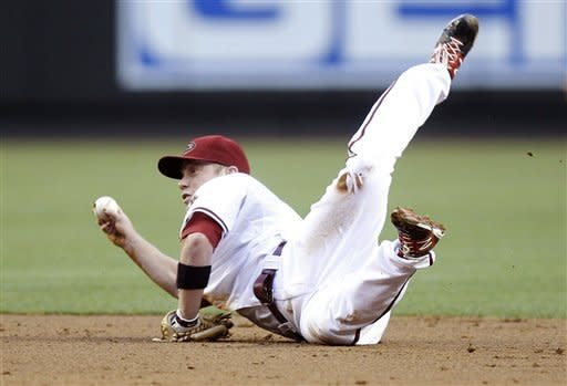Arizona Diamondbacks second baseman Aaron Hill looks to flip the ball to shortstop Willie Bloomquist to force out San Francisco Giants' Hector Sanchez at second base in the second inning of a baseball game, Friday, May 11, 2012, in Phoenix. (AP Photo/Paul Connors)