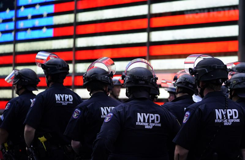 "NYPD police officers watch demonstrators in Times Square on June 1, 2020, during a ""Black Lives Matter"" protest."