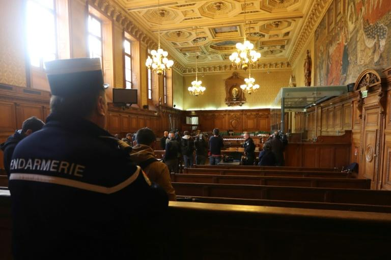 """A gendarme looks towards reporters in the courtroom of a Special Court of Assizes at the Paris courthouse, prior to the start of the trial of a jihadist network known as the """"Cannes-Torcy cell"""", on April 20, 2017"""