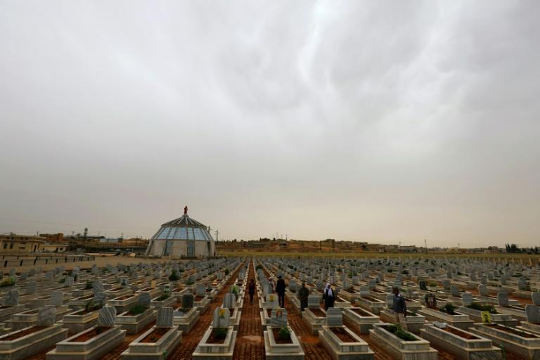 Hundreds of identical tombs are arranged in rows at the Martyrs' Ceremony in the Syrian Kurdish town of Kobane