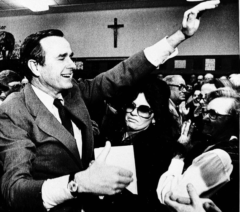 George Bush waves to acknowledge the applause of Iowa voters in the St. Augustin's precinct of Des Moines after he won a majority of votes there, Jan. 21, 1980.