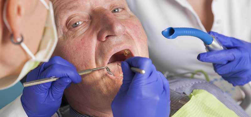 Elderly man getting a dental exam.