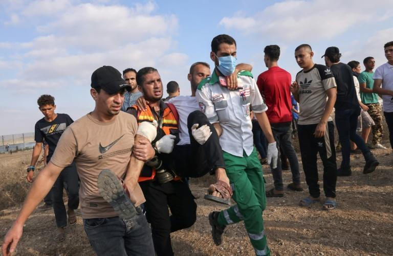 Palestinian medics and protesters evacuate an injured man hurt in clashes with Israeli security forces on Saturday