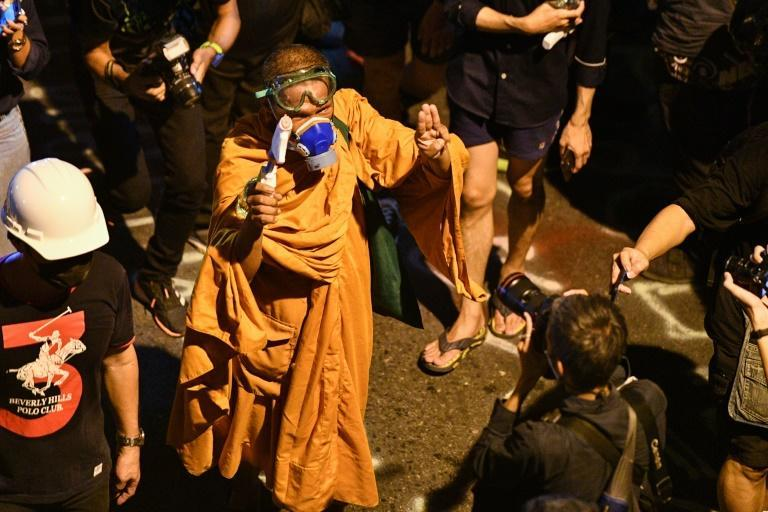 A man wearing monk robes and a gas mask carries a water pistol as he holds up the three-finger salute during an anti-government rally in Bangkok on November 18, 2020