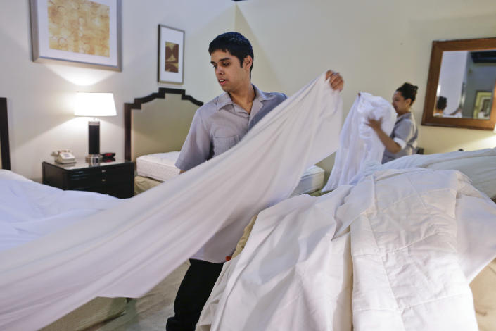 Nemias Ayala, left, and Mailen Gonzales practice stripping and making hotel room beds in a guest room attendant class at the Culinary Academy of Las Vegas Friday, Dec. 14, 2012, in Las Vegas. The academy is funded through a trust created by culinary and bartenders unions as well as management from 26 properties on the Las Vegas Strip. Nevada has become an increasingly Democratic state. And the Culinary Union's track record gives a dispirited labor movement some hope even as it continues to hemorrhage workers and reels from the signature of a right-to-work law in Michigan this week. (AP Photo/Julie Jacobson)