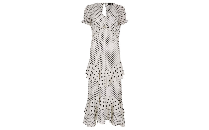 """Who said you can't tackle the dress code while looking after your pennies? We'll be teaming this polka dot number with a red lip and '90s strappy heels. <a href=""""https://www.riverisland.com/p/white-and-black-spot-print-frill-maxi-dress-734063?t168=t168-search-plp"""" rel=""""nofollow noopener"""" target=""""_blank"""" data-ylk=""""slk:Shop now"""" class=""""link rapid-noclick-resp""""><em>Shop now</em></a>."""