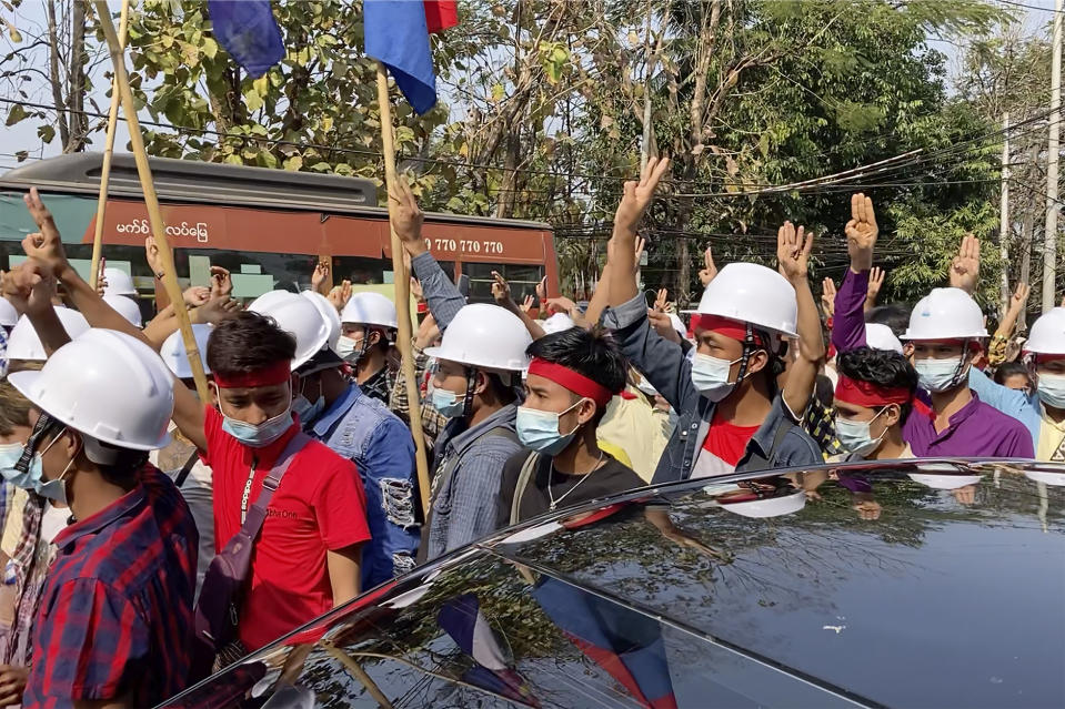 In this image from video, protesters wearing hard hats flash the three-fingered salute while they march in Yangon, Myanmar Saturday, Feb. 6, 2021. The military authorities in charge of Myanmar broadened a ban on social media following this week's coup, shutting access to Twitter and Instagram, while street protests continued to expand Saturday as people gathered again to show their opposition to the army takeover. (AP Photo)