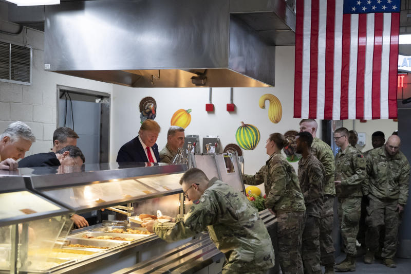 President Donald Trump accompanied by Joint Chiefs Chairman Gen. Mark Milley, right, serves dinner during a surprise Thanksgiving Day visit to the troops, Thursday, Nov. 28, 2019, at Bagram Air Field, Afghanistan. (AP Photo/Alex Brandon)
