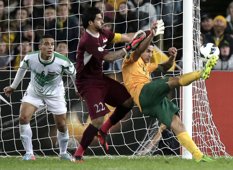 Australia's Tim Cahill, right, attempts to score on Iraq's Noor Sabri Abbas as Iraq's Aliadnan Kadhim, left, guards the goal during their World Cup soccer Asian qualifying match at the Sydney Olympic Stadium in Sydney, Australia, Tuesday, June 18, 2013. (AP Photo/Rick Rycroft)